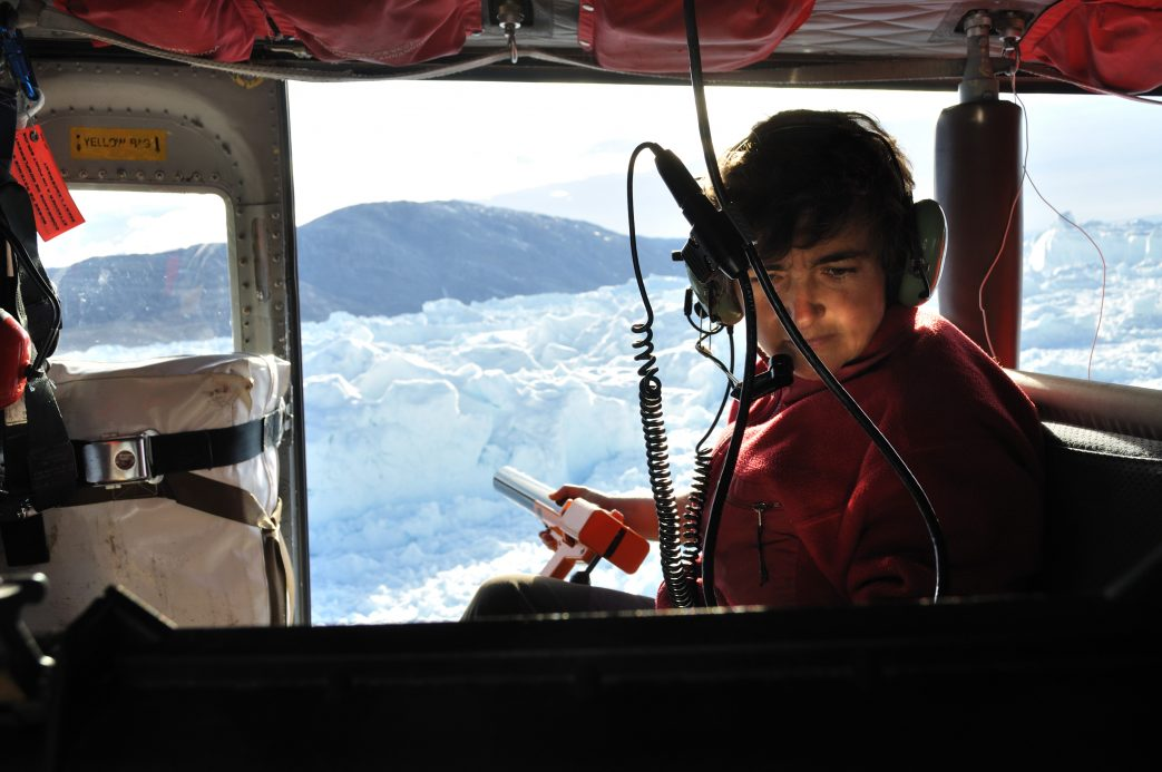 Fiamma Straneo flying above a glacier in a helicopter